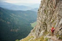 Caminante solitario que camina abajo de un rastro de montaña rugoso Fotografía de archivo libre de regalías