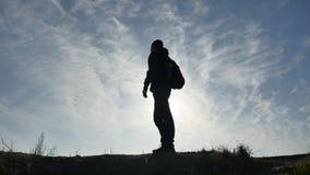 Caminante turístico del hombre de la luz del sol de las siluetas con las mochilas que disfruta de la opinión de la puesta del sol almacen de video