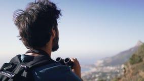 Caminante usando los prismáticos mientras que se opone al cielo metrajes