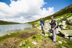 Caminantes cerca un lago en las montañas Fotos de archivo libres de regalías