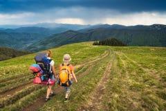 Caminantes de la familia en un camino en un valle de la montaña Imagenes de archivo