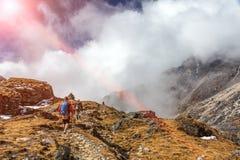 Caminantes de la montaña que caminan el las nubes hermosas y Sun del terreno herboso Fotos de archivo libres de regalías
