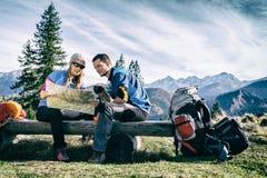 Caminantes de los pares con el mapa en montañas imágenes de archivo libres de regalías