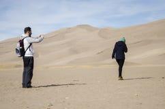 Caminantes en el grandes parque nacional y coto de las dunas de arena Fotos de archivo
