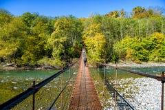 Caminantes en el puente del pie de la suspensión sobre el río de la montaña foto de archivo libre de regalías
