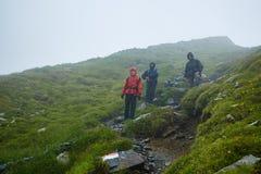 Caminantes en impermeables en la montaña Imagen de archivo