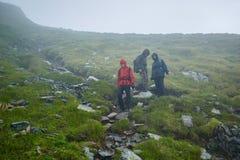 Caminantes en impermeables en la montaña Fotografía de archivo libre de regalías