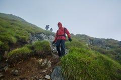 Caminantes en impermeables en la montaña Fotos de archivo