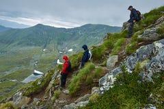 Caminantes en impermeables en la montaña Imagenes de archivo