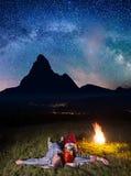 Caminantes felices de los pares que admiran las estrellas brillantes y que mienten cerca del fuego en la noche Exposición larga Fotos de archivo libres de regalías