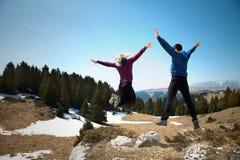 Caminantes felices que saltan en el top de la montaña foto de archivo