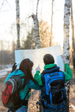 Caminantes jovenes de los pares que miran el mapa Imagen de archivo libre de regalías