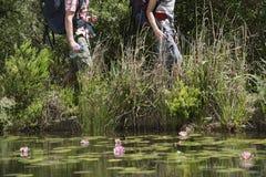Caminantes masculinos que caminan por el lago Imágenes de archivo libres de regalías
