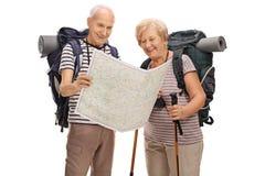 Caminantes mayores que miran el mapa genérico Imagen de archivo libre de regalías