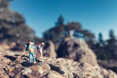 Caminantes miniatura con las mochilas Imagen de archivo