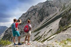 Caminantes que caminan en alza en paisaje de la naturaleza de la montaña y que toman las fotos Fotografía de archivo libre de regalías