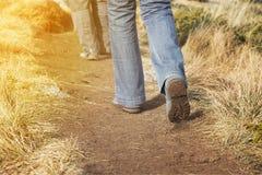 Caminantes que caminan a lo largo de un sendero arenoso de la montaña Imagen de archivo