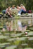 Caminantes que leen el mapa por el lago Foto de archivo libre de regalías