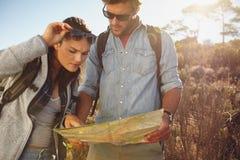 Caminantes que miran el mapa para la navegación Imágenes de archivo libres de regalías