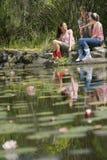 Caminantes que se relajan por el lago Imagen de archivo