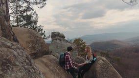 Caminantes románticos que se sientan en el top de la montaña, charlando, y disfrutando de su tiempo junto Un muchacho con una sup almacen de metraje de vídeo