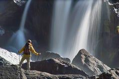 Caminar al hombre con la mochila que mira la cascada Fotos de archivo libres de regalías