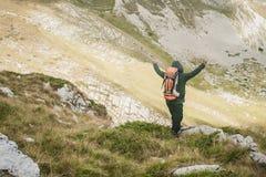 Caminar al hombre con los brazos abiertos del backpacker que miran picos de montaña imagen de archivo libre de regalías