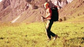 Caminar al hombre que camina en prado verde de la montaña con la mochila Deporte del verano y concepto de la reconstrucción metrajes
