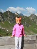 Caminar al niño con la máscara del zorro en las montañas Imagenes de archivo