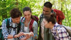 Caminar a amigos con las mochilas y smartphone metrajes