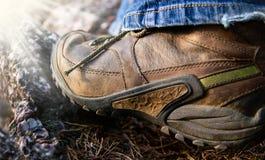 Caminar botas en la acción al aire libre que sube en piedra Fotos de archivo libres de regalías