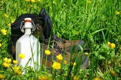 Caminar botas en un prado del verano Fotografía de archivo