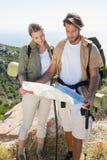 Caminar el mapa de la lectura de los pares en la cumbre de la montaña Foto de archivo