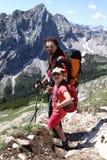 Caminar el niño y al padre del senderismo en las montañas Imagenes de archivo