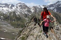 Caminar el niño y al padre del senderismo en las montañas, Austria Foto de archivo libre de regalías
