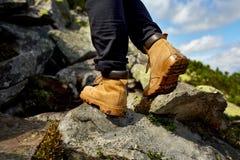 Caminar el primer de las botas pasos turísticos de la muchacha en el rastro de montaña en las rocas Fotos de archivo libres de regalías