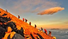 Caminar junto el pico de la gente de la subida de la montaña Foto de archivo libre de regalías