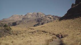 Caminar a la muchacha con la mochila que camina en las montañas almacen de metraje de vídeo