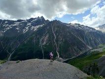Caminar la muchacha en las montañas, el sentido de la libertad y aventuras imágenes de archivo libres de regalías
