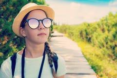Caminar a la muchacha turística adolescente en gafas de sol en las montañas Fotos de archivo libres de regalías