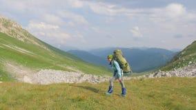 Caminar a la mujer con la mochila que viaja en montaña El subir y turismo del verano almacen de video