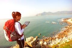 Caminar la tableta digital del uso de la playa del soporte de la mujer Fotografía de archivo