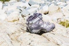 Caminar las botas que se colocan en las piedras Imagenes de archivo