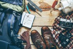 Caminar los accesorios turísticos en fondo de madera, visión superior Concepto de las vacaciones del descubrimiento de la aventur Imagen de archivo libre de regalías