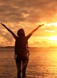 Caminar los brazos aumentados mujer a la salida del sol Foto de archivo