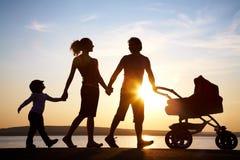 Caminata de la familia en la puesta del sol Fotografía de archivo libre de regalías