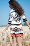 Caminata de la mujer en campo de trigo en día de verano asoleado. Fotos de archivo libres de regalías