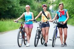 Caminata de tres mujeres con la bicicleta Imagen de archivo