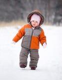 Caminata del bebé por el camino de la nieve en parque Imagen de archivo