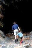 Caminata del padre y del hijo en la cueva Fotos de archivo